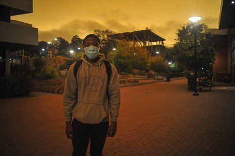 Student in face mask on Contra Costa College campus under darkened yellowish-brown sky.