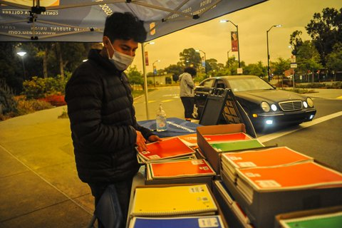 Young man in face mask looks at notebooks of different colors. Nearby, someone stands by a black Mercedes-Benz. Sky is yellowish-brown.