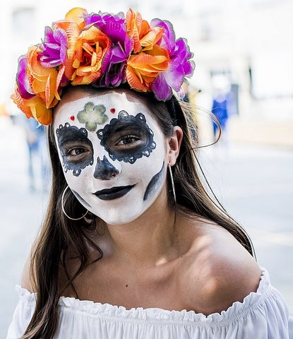 A young woman wearing skull face makeup and a headdress of orange and purple flowers.