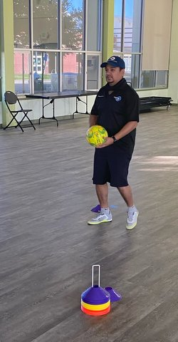 A man standing in the middle of a room with large windows holding a neon yellow soccer ball.