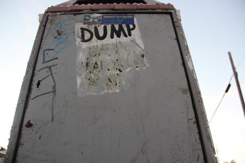 "View looking up from the ground of a trash can with sticker that says ""DUMP"" on it."