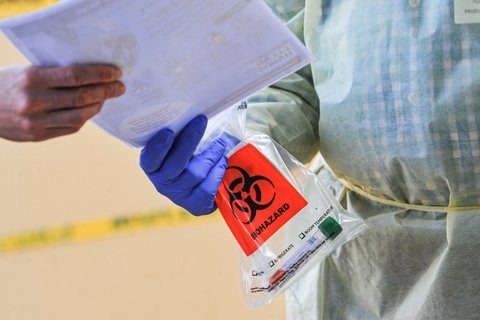 Close up of person in medical gown and purple glove holding biohazard bag and handing paper to another person.