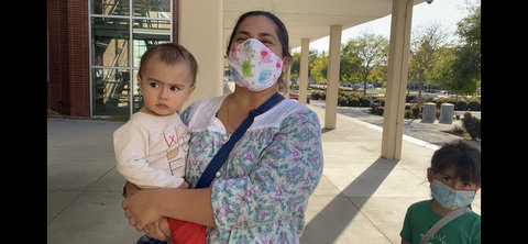 A woman wearing a face mask and holding a baby with a small child wearing a mask next to her.