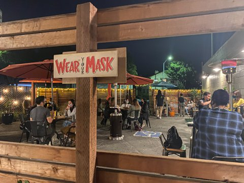 "People dining on restaurant patio with sign that says ""Wear Your Mask."""