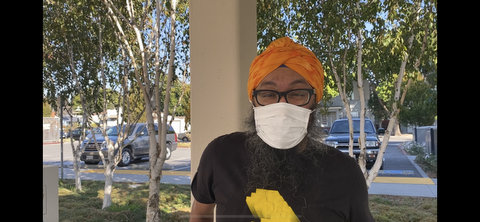 An Indian man in T-shirt, white face mask, black-rimmed glasses and orange turban.