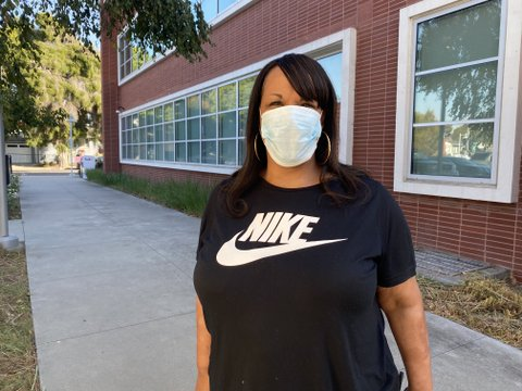 A Black woman wearing a face mask and Nike T-shirt.