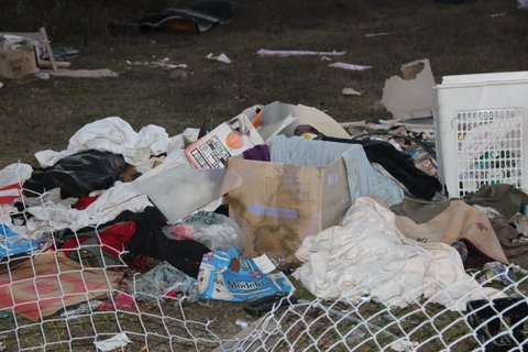 A pile of garbage including a laundry hamper behind a downed chain-link fence.