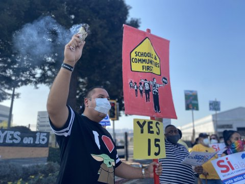 "A man in medical face mask holds one sign that says ""yes 15"" and one that says ""schools and communities first"" with a drawing of kids and a crossing guard holding a ""stop"" sign that says ""vote."" The man is wearing a black shirt with the letter ""I"" and drawings of a heart and Baby Yoda."