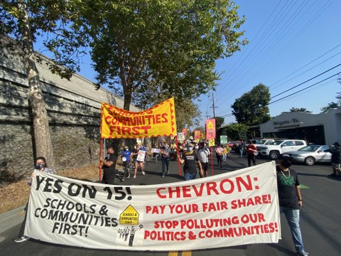 "Protest march led by two people with banner that reads ""Yes on 15! Schools and communities first! Chevron: Pay your fair share! Stop polluting our politics and communities!"""