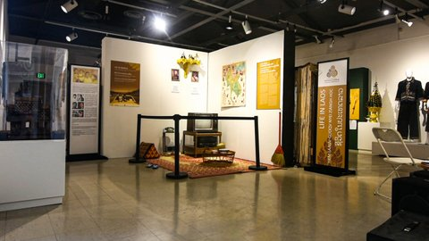 """Museum exhibit with old TV, rotary phone, broom, flip-flops and more near sign that says """"Life in Laos"""""""
