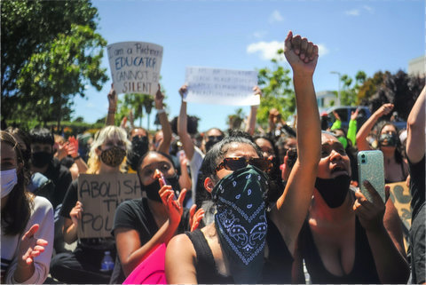 Crowd of protesters, some wearing masks and some with signs. Front and center is a person with their fist in the air and wearing sunglasses and a black bandanna over their face.