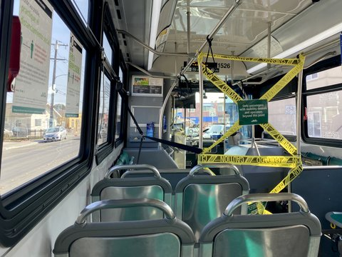 """Interior of a bus with section blocked by caution tape and sign that says """"Only passengers with mobility devices and operators beyond this point"""""""
