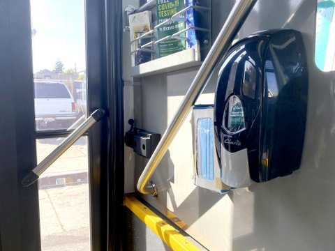 Dispensers for hand sanitizer and masks near back door of a bus.
