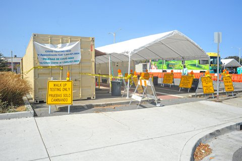 Parking lot with tent covering, mobile health clinic and signs for coronavirus testing