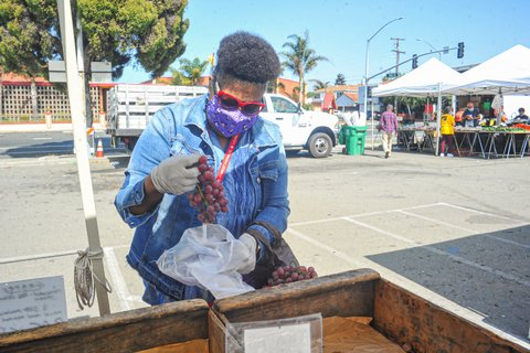 A Black woman in face mask and orange sunglasses puts a bunch of red grapes into a plastic bag.