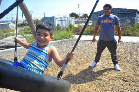 A smiling little boy on a tire-shaped swing in a park with his dad, wearing a UC Berkeley T-shirt, standing a few feet behind him.