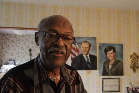 An older balding Black man wearing glasses with paintings of a Black man and woman behind him.