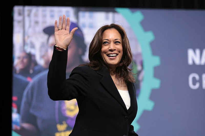 Kamala Harris smiling and waving.