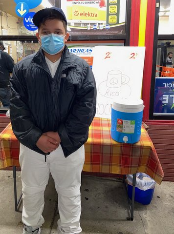 Boy in coat, face mask and cap stands in front of a small table in front of a business.