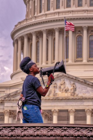 Black person with bullhorn in front of U.S. Capitol