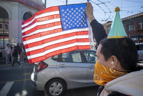 Person wearing a party hat and orange bandana holds up a U.S. flag