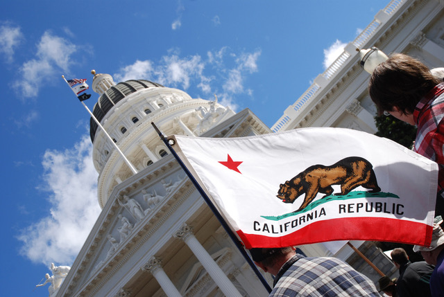 Upward angled view of the California State Capitol with person holding the California flag in the foreground.