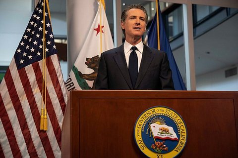 Gov. Gavin Newsom at lectern with California seal in front of U.S. and California flags
