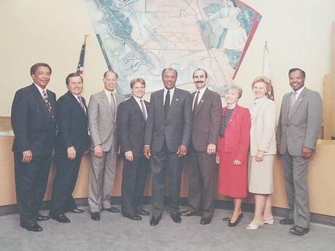 Seven men and two women in suits standing in a row