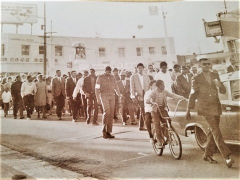 Sepia-toned photo of several Black people walking on a Richmond street in protest.