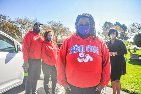 A Black woman in a Fresno state sweatshirt and Nike face mask. A Black man and two Black women are standing behind her.