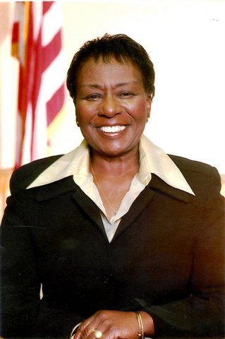 Irma Anderson, a smiling Black woman in a suit, with U.S. flag in background