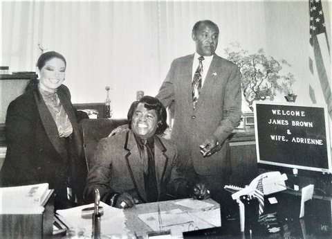 Black-and-white photo of James Brown, his wife Adrienne, and Mayor George Livingston