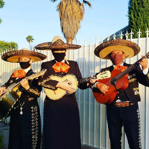 Three mariachis wearing sombreros and face masks