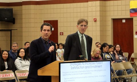 "A man at a lectern next to another man in front of people in folding chairs. A screen say ""strategies to increase parent satisfaction and enrollment."""