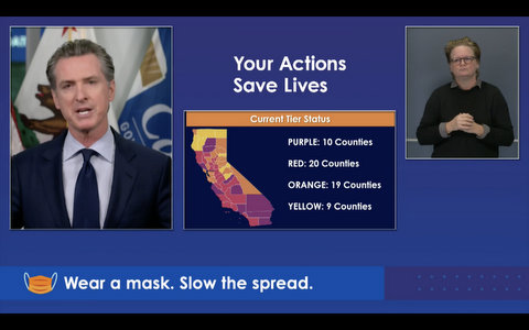 Screenshot with Gavin Newsom, ASL interpreter and color-coded California map. Text reads: Your action saves lives; purple: 10 counties; red: 20 counties; orange: 19 counties; yellow: 9 counties; wear a mask. Slow the spread.