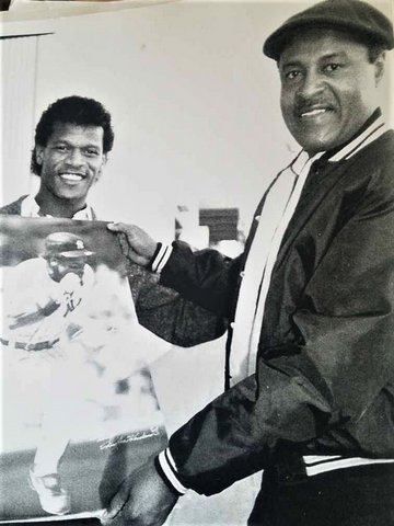 Black-and-white photo of Rickey Henderson and another Black man holding a photo of Henderson running the bases