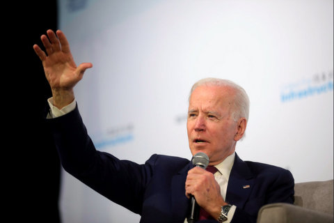 Joe Biden standing with a microphone in his left hand and his right arm outstretched.