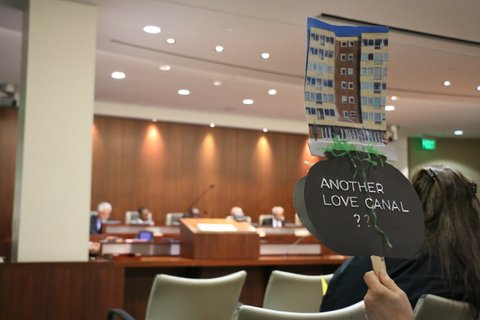 "Person at City Council meeting holding up picture of building with words ""Another love canal?"""