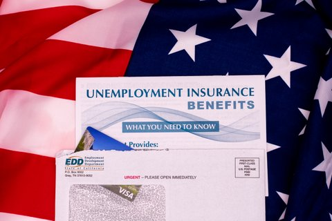 Text: Unemployment Insurance Benefits What You Need to Know. EDD envelope against U.S. flag