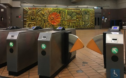 Fare gates and mural at a BART station