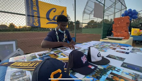 Young Black man at table with photos and ball caps in front of Cal Golden Beats banner