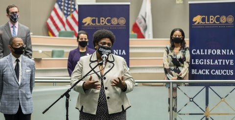 "Black woman wearing at a microphone wearing mask that says ""California Safe."" Behind her are four people in masks spread out and a California Black Legislative Caucus sign."