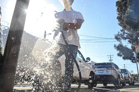 Ground-level view of person spraying a hose.