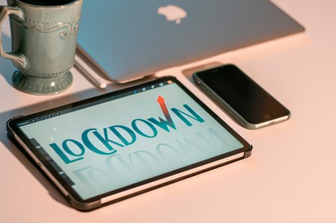"A tablet with the word ""lockdown"" on the screen next to a smartphone, MacBook and coffee mug."
