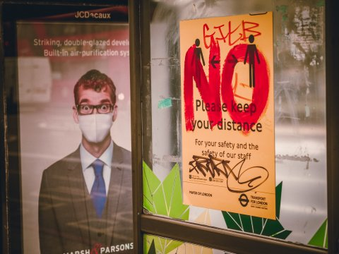 """NO"" in big red letters and graffiti on sign that says ""please keep your distance"" next to poster with man in face mask"