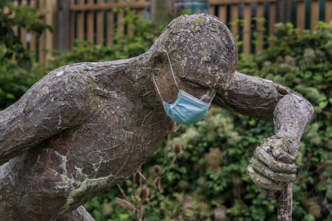Statue of a man with a surgical mask on its face