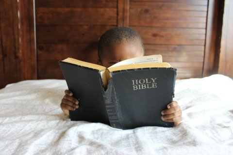 An African American boy in bed reading the Bible.