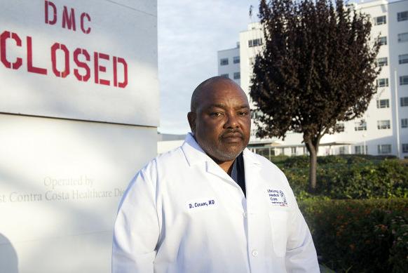 "Black man in lab coat near wall that says ""DMC CLOSED"""