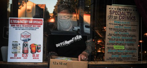 Woman in face mask seen through glass between signs