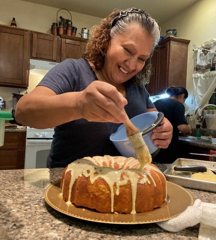 Smiling woman ices a bundt cake in her kitchen